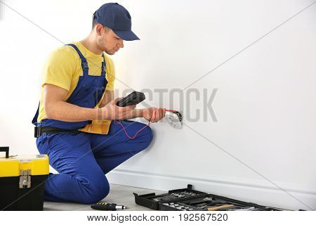 Electrician measuring voltage of socket indoors