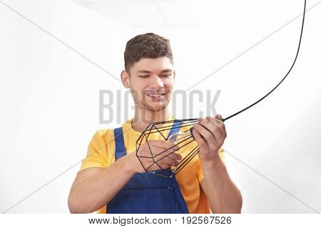 Young electrician changing electric light bulb indoors