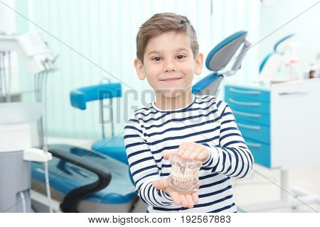 Cute little boy with plastic jaw mockup at dentist's office