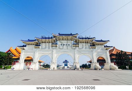 Archway of Chiang Kai Shek Memorial Hall in Tapiei (close to MRT) on sunny day with tourists and pigeons the landmark for tourist attraction in Taiwan.