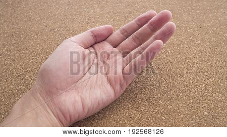 Upturned left hands for holding something on cork wood background