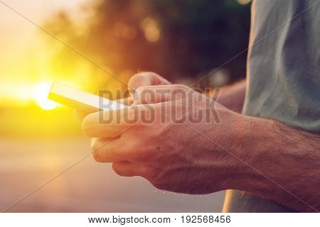 Man using mobile phone on street in sunset close up of hands and thumbs typing message