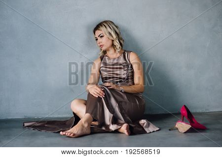 Beautiful young woman in stylish long purple dress and purple shoes sitting on a floor in a studio