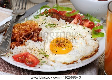 Breakfast - Soft boiled rice with scrambled eggs bacon tomato slices and greens