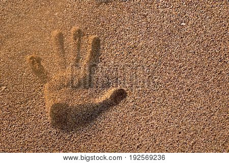 Handprint in the sand and sun set