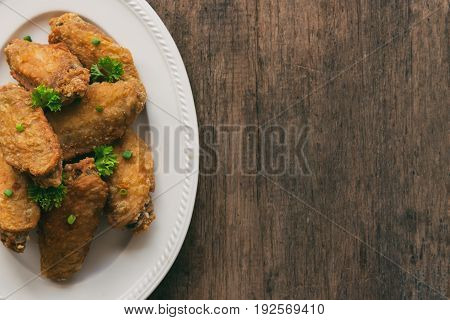 Fried chicken wings served with barbecue dipping sauce. Homemade fried chicken delicious and crispy. Top view with copy space on fried chicken and chili sauce or tomato sauce (ketchup)ready to served. Deep fried chicken wings. Street food background.