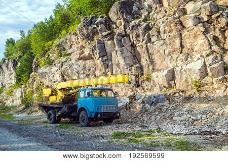Old yellow automobile crane with blue cab and telescopic boom in transport position near with rocky mountain