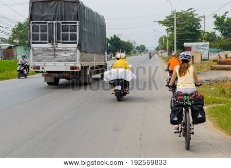 Girl traveling by bicycle with side bags on the roads of Vietnam