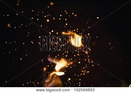sparks from fire in fireplace with bokeh balls, shallow focus