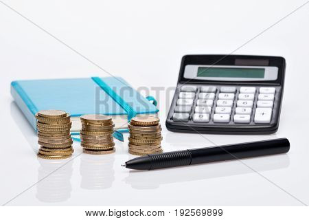Coin Pile, Pocket Calculator And Notebook