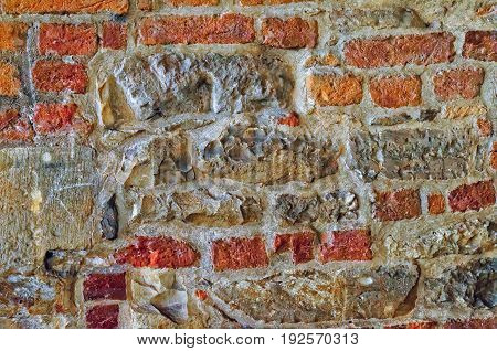The Wall Built Of Irregular Stones And Bricks Background. Texture Of Old Stonework. Space For Text.