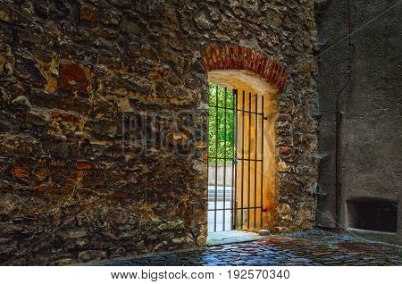 Door with metal grating in ancient wall made or rough irregular stones