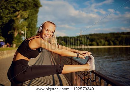 The girl warmes up in the park. Young woman with a smile doing a warm-up before training in a park by the lake.
