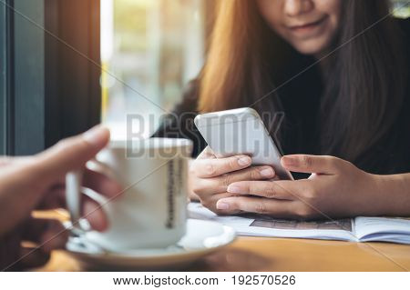 A beautiful Asian woman using and looking at smart phone in the cafe with a hand holding a cup of coffee foreground