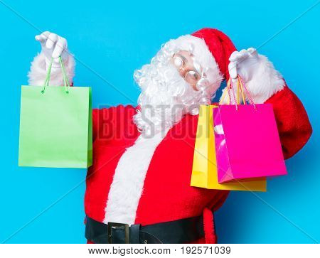 Funny Santa Claus have a fun with shopping bags on blue background