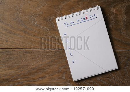 to do in 2018 year list on notepad on wood background, with copy space