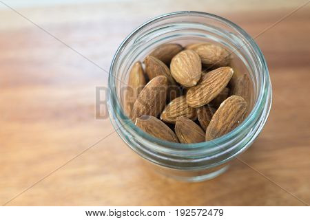 Almonds in glass bottles on brown wooden background