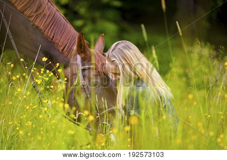 Smiling young woman sits in the in field with her large arabian horse. Relationship and connection between human and animal.