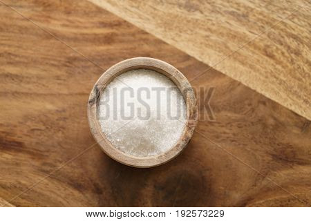 sugar in wood bowl on wooden table from above, with copy space
