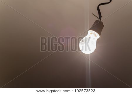Close up burning light bulb hanging from ceiling