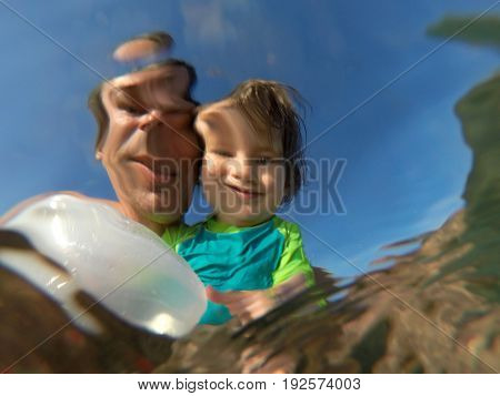 Underwater View Of A Father And Her Daughter With Distorted Faces Having Fun At The Sea