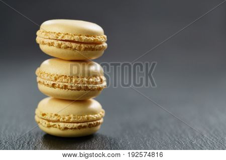 lemon yellow macarons stacked on slate board with copy space