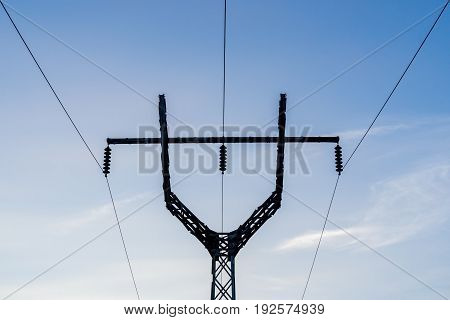 High voltage tricorn power line silhouette on sky background