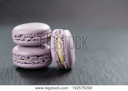 lavender purple macarons stacked on slate board with copy space