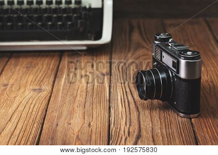 Old camera and typewriter on old wooden background. copy space. concept