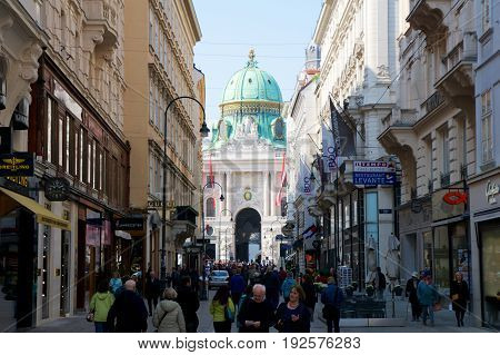 VIENNA, AUSTRIA - APR 29th, 2017: Famous entrance of the Hofburg Palace in Vienna as seen from the pedestrian zone Kohlmarkt. It was the Habsburgs' principal winter residence, currently serves as the residence of the President of Austria