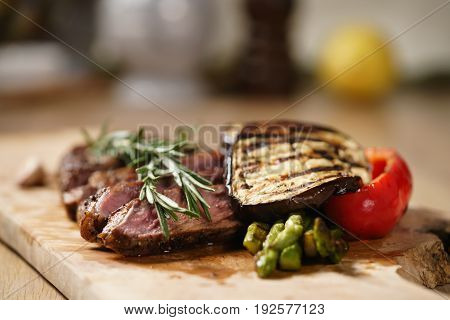 sliced medium rib eye steak with grilled vegetables, shallow focus