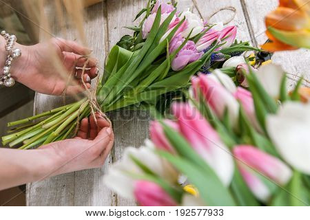 Woman packing tulip bouquet top view. Unrecognizable florist make floristry assemble in workshop on wooden background