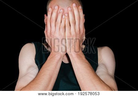 Depression. Depressed man cover his face with his hands. Isolated on black background. Loneliness. Sadness. Abuse.