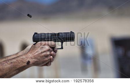 Pair of hands holding a handgun as it is being shot