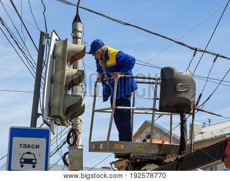 Voronezh, Russia - April 27, 2017: The employee of city services serves a traffic light on Lenin's area