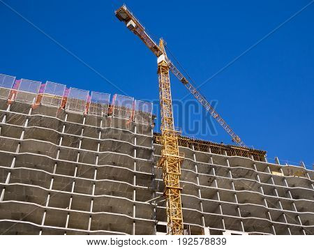 The frame of a monolithic apartment house and a nearby tower crane