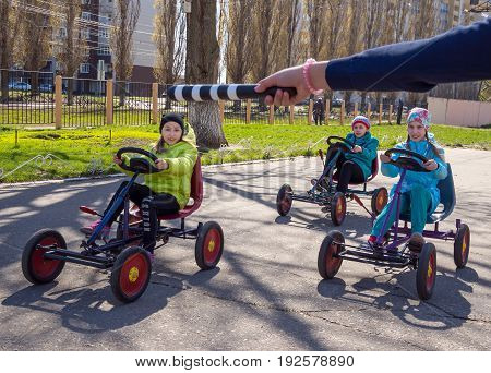Voronezh, Russia - April 26, 2017: Children on toy cars execute commands of the regulator