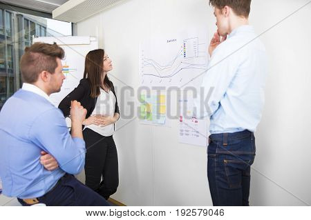 Male and female business professionals discussing over line graph in office