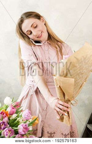 Florist pack festive bouquet and talk at phone. Young beautiful florist make floristry assemble with pink peony and wildflowers in workshop on wooden background