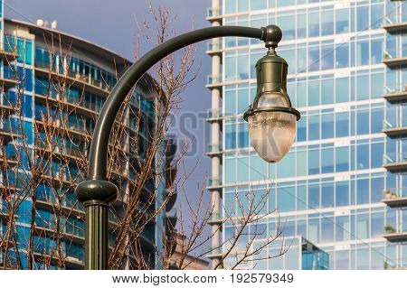 A streetlight on the background of bare trees and skyscrapers Atlanta USA