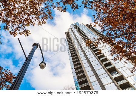 Bottom view of streetlight and skyscraper on the background of cloudy sky in autumn day Atlanta USA