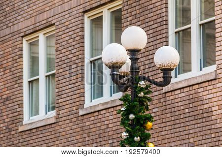 A streetlight with Christmas decorations on the background of a brick facade Atlanta USA