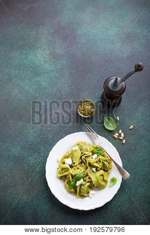 Homemade Italian tortelloni with green pesto, goat cheese and pine nuts on white plate on green stone background. Healthy food concept. Copy space. High angle view.