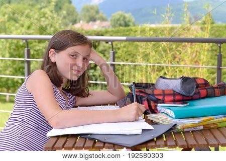 A pretty young teenager doing her homework