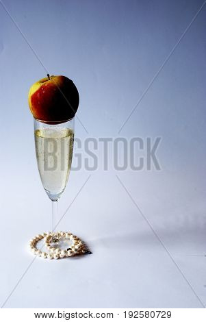 Champagne, pearls and an apple in a white background