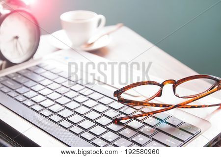 Shallow depth of field closeup of editor's workspace with eyeglasses laptop coffee cup and alarm clock