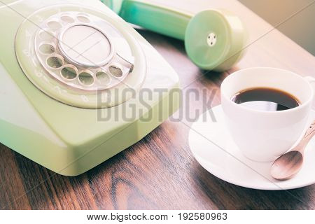 Cup of coffee with old green phone on wooden table Retro style concept
