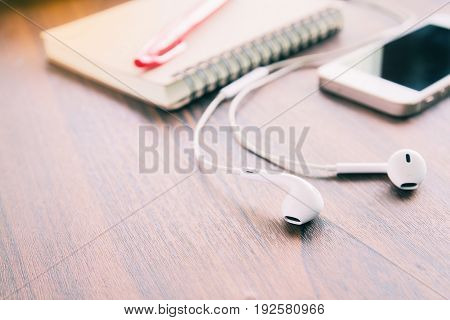 earphones smartphone notebook and red pen on wooden table selective focus on earphones