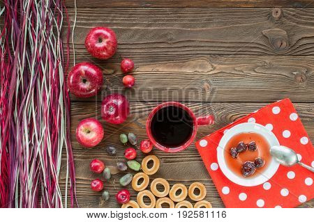 red cup of tea ripe red apples actinidia berries bagels strawberry jam in white saucer spoon red napkin at white polka dots on wooden table with decorative colorful dry straw. top view