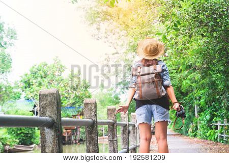 Hipster asian girl with camera breathing and looking at tropical walkway and canal Tourist Traveler in Asia location